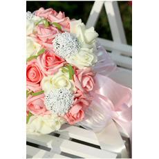 Une main de mariée avec un bouquet de 30 roses pleines d'étoiles